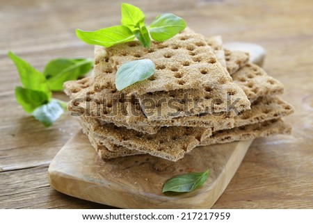 Dry flat bread crisps with herbs on a wooden board - stock photo