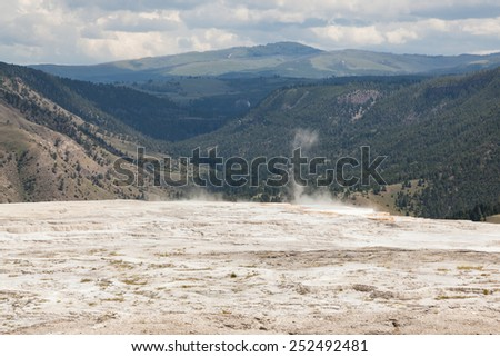 Dry flats of mineral formations lead up to a ledge where hot water and steam flow over the ledge of Mammoth Hot Springs with distant mountains and clouds at Yellowstone National Park. - stock photo