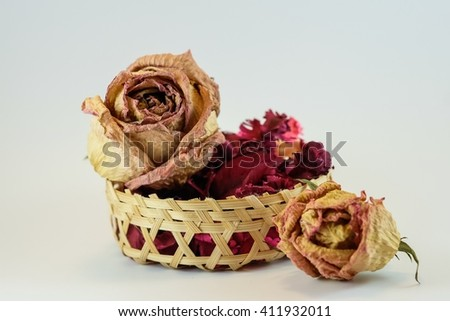 Dry flower in small basket on white background - stock photo