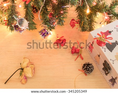 Dry flower, red christmas bells and gift present with christmas tree on wooden background in warm tone
