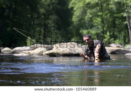Dry fly fishing. Fly fishermen in a French trout river. Fisherman fight against a big trout - stock photo