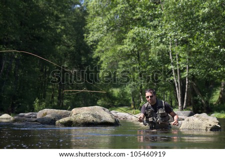 Dry fly fishing. Fly fishermen in a French trout river. Fly fishing casting scene - stock photo