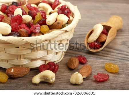 dry fruit with nuts on wooden background - stock photo