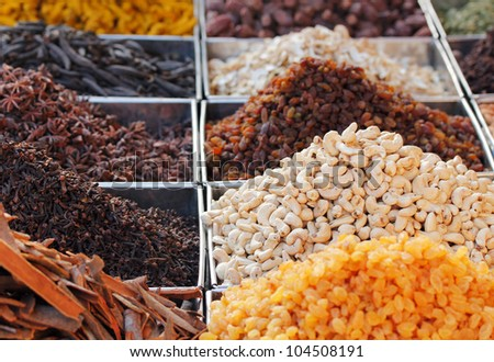 Dry fruits and spices like cashews, raisins, cloves, anise, etc. on display for sale in a bazaar in bangalore, india. - stock photo