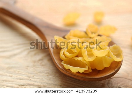 Dry gnocchi pasta in wooden spoon on a table - stock photo