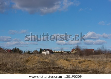 Dry grass landscape with houses on the background