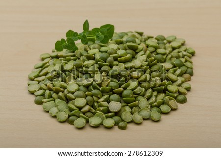 Dry green peas heap on the wood background - stock photo