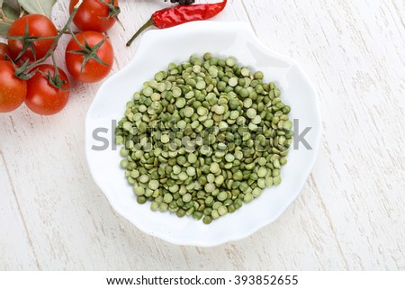 Dry green peas in the bowl on wood background - stock photo