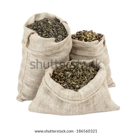 Dry green tea in fabric bags isolated on white background. Dragon pearls, Ginseng Wu Long, leaves - stock photo