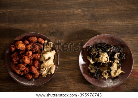 dry  herb Chinese jujube ginger mushroom on brown dish wood table