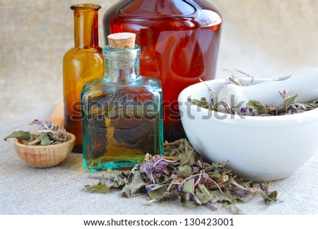 Dry herbal tea Chamerion is with tinctures in bottles on sackcloth, herbal medicine - stock photo