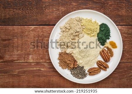 dry ingredients of healthy breakfast smoothie: whey protein, cacao, chia seeds, pecan nuts, maca root powder, spirulina,  spices (cinnamon, ginger, turmeric) on a rustic wooden table - stock photo