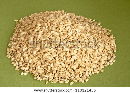 Dry integral rice on green textured background - stock photo