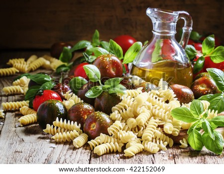 Dry Italian pasta spiraline, green basil, olive oil in a jug, black and red cherry tomatoes, still life in rustic style on a vintage wooden background, selective focus - stock photo