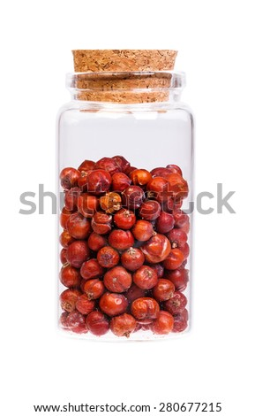 Dry Juniper seed in a bottle with cork stopper for medical use. - stock photo