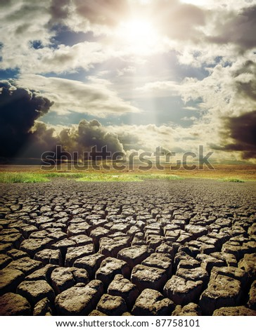 dry lake and dramatic sky with sun - stock photo