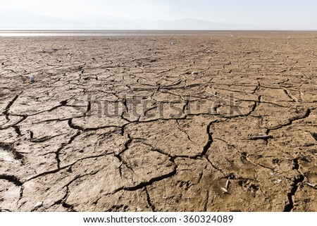 Dry lake bed with natural texture of cracked clay in perspective floor. Death Valley field . background. Selective focus on black soil dark land. Idea concept symbol disaster ecology in nature