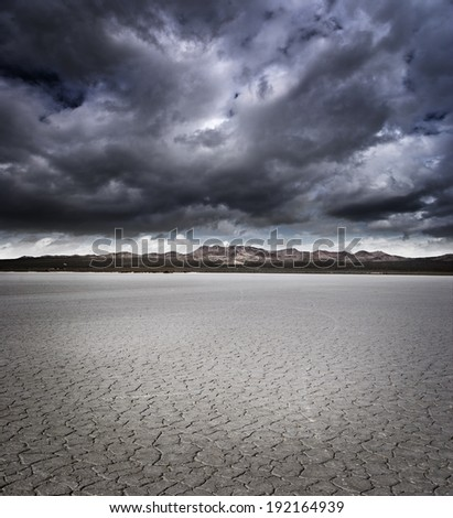 Dry lake bed with storm clouds - stock photo