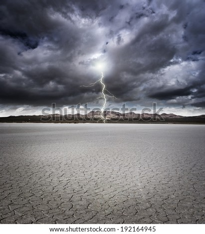 Dry lake bed with storm clouds and lightning  - stock photo