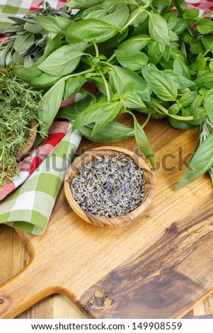 Dry  Lavender and other  herbs in olive wood bowl . Herbs in olive wood bowl on wooden  background. Copy space composition - stock photo
