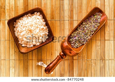 Dry lavender flower seeds in a traditional wood scoop and natural bath salts crystals in a wooden dish in an aromatherapy spa over bamboo mat background