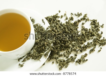 Dry leaves of green tea on white background - stock photo