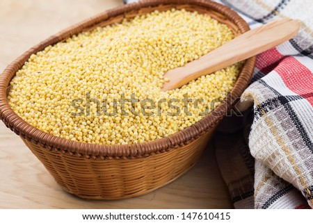 Dry millet in wooden bowl on colorful towel. Selective focus. - stock photo