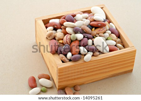 Dry mixed beans in a wooden box resting on textured paper.