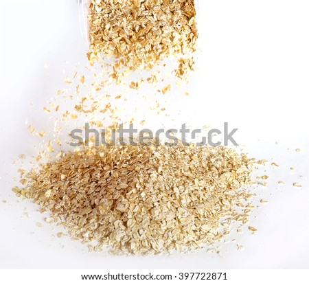 Dry oat flakes falling on a white background