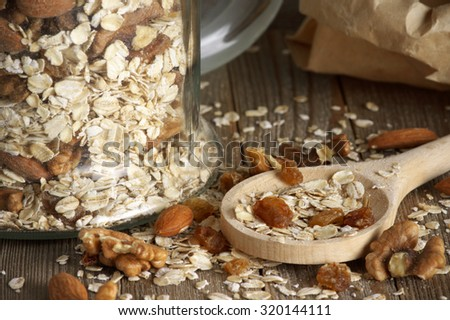 Dry oatmeal flakes with walnuts, almonds and raisins in glass jar and wooden spoon close-up. Shallow DOF. - stock photo