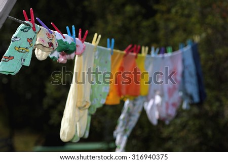 dry on a rope baby clothes - stock photo