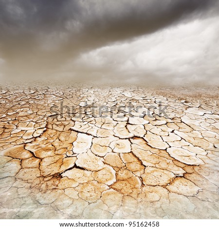 Dry, parched cracked earth with stormy dusty sky and foreground water