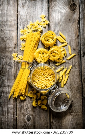 Dry pasta in cans and mixed the pasta with spaghetti. On wooden background. Top view - stock photo