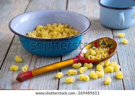 dry pasta on a wooden table in an iron bowl with a wooden spoon - stock photo