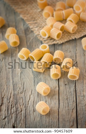 Dry pasta on wooden background - stock photo