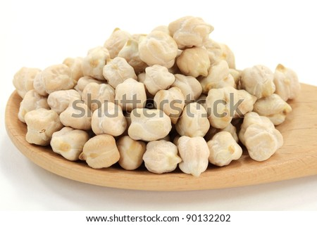 Dry Raw Chick Peas Seeds (very rich of proteins) spilled on pile in wooden cooking spoon over white background. - stock photo