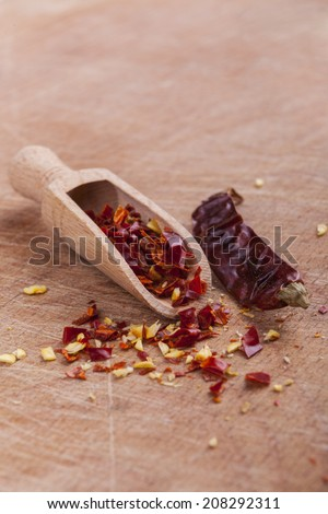 Dry red hot chili peppers with wooden spoon on brown wood background - stock photo
