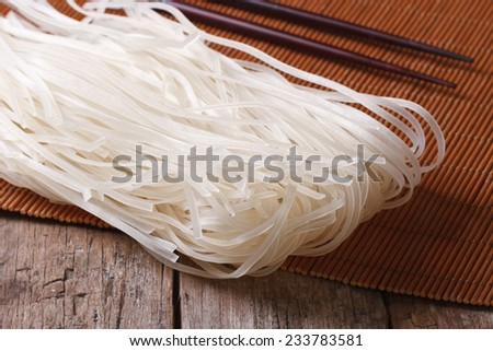 Dry rice noodles with chopsticks close up on the table. horizontal  - stock photo