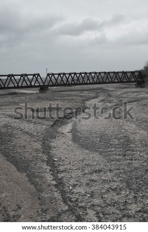 Dry rocky river bed crossed by an industrial bridge