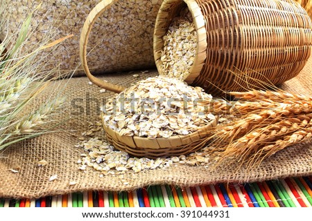 Dry rolled oatmeal flakes bamboo basket with oats ears on jute cloth