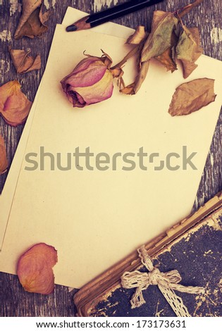 Dry rose and old book on a wooden background with space for information (Vintage) - stock photo
