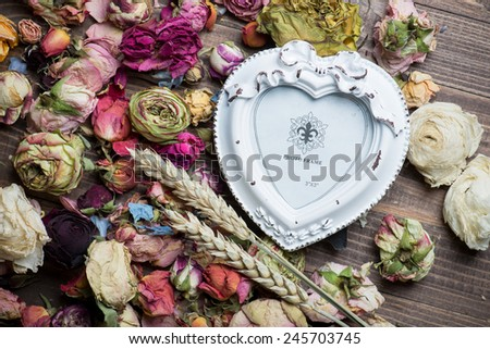 Dry rose flowers heart on wood panel. Valentines background. - stock photo