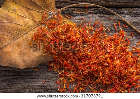 Dry Safflower with leaf  on grunge wooden background. - stock photo