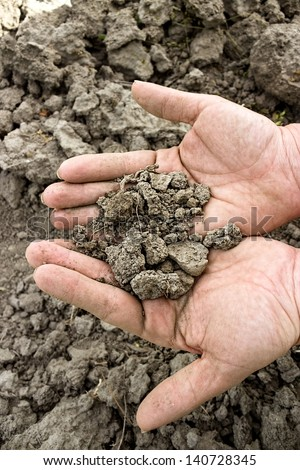 dry soil in hands over cracked land - stock photo
