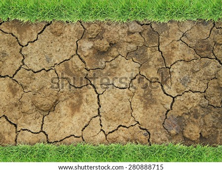 Dry soil with green grass border - stock photo
