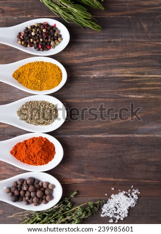 Dry spices in spoons and green herbs on the wooden table, top view - stock photo