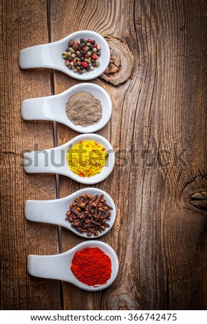 Dry spices in spoons on the wooden table, top view. - stock photo