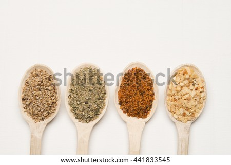 Dry spices on a wood spoons against white background - stock photo