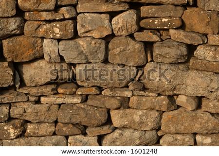 Dry Stone Wall Background Texture Digitally mixed orange cast. - stock photo