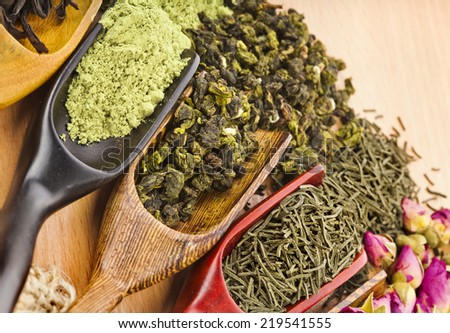 dry tea in scoops close up on wooden table background top view  - stock photo
